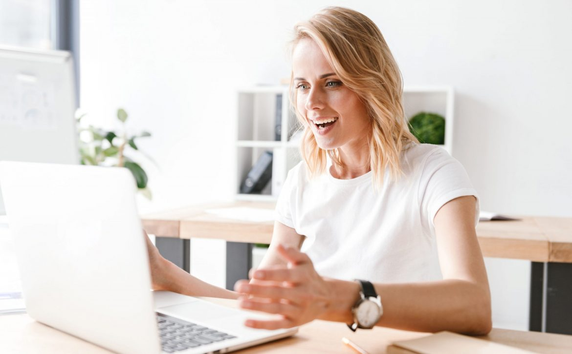 Excited businesswoman working on laptop computer